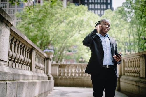 Smiling African American man talking on smartphone with wireless earphones in park