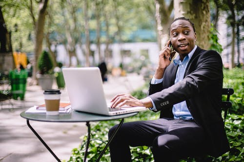 Cheerful young African American male entrepreneur having phone call while working remotely on laptop in street cafe on sunny day