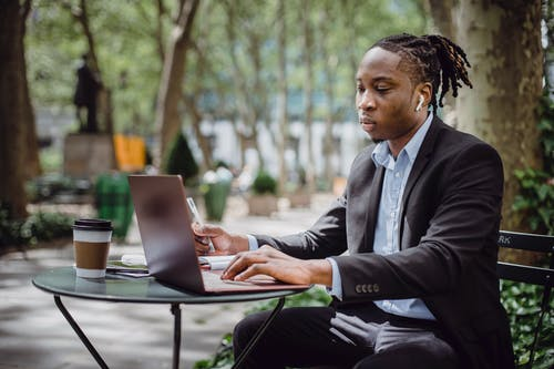 Busy young African American man with dreadlocks working on laptop in street cafe