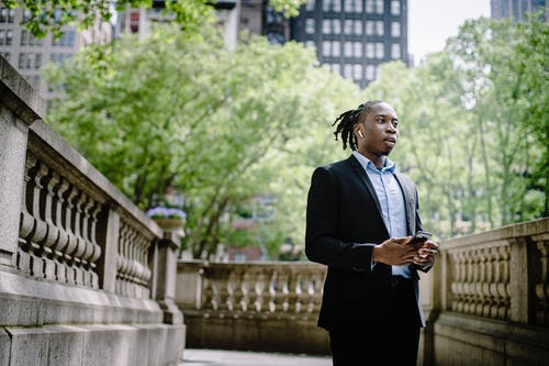 Pensive black male talking on smartphone with TWS earphones in downtown