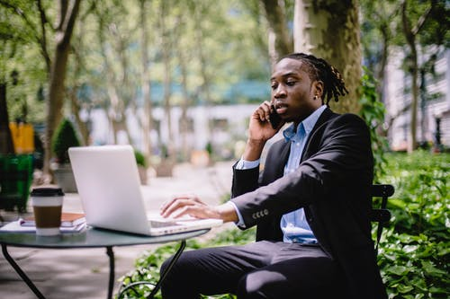 Serious stylish young African American male manager in formal wear browsing laptop while having phone call in outdoor cafe