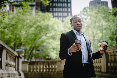 Positive young black man with smartphone and takeaway coffee in city park