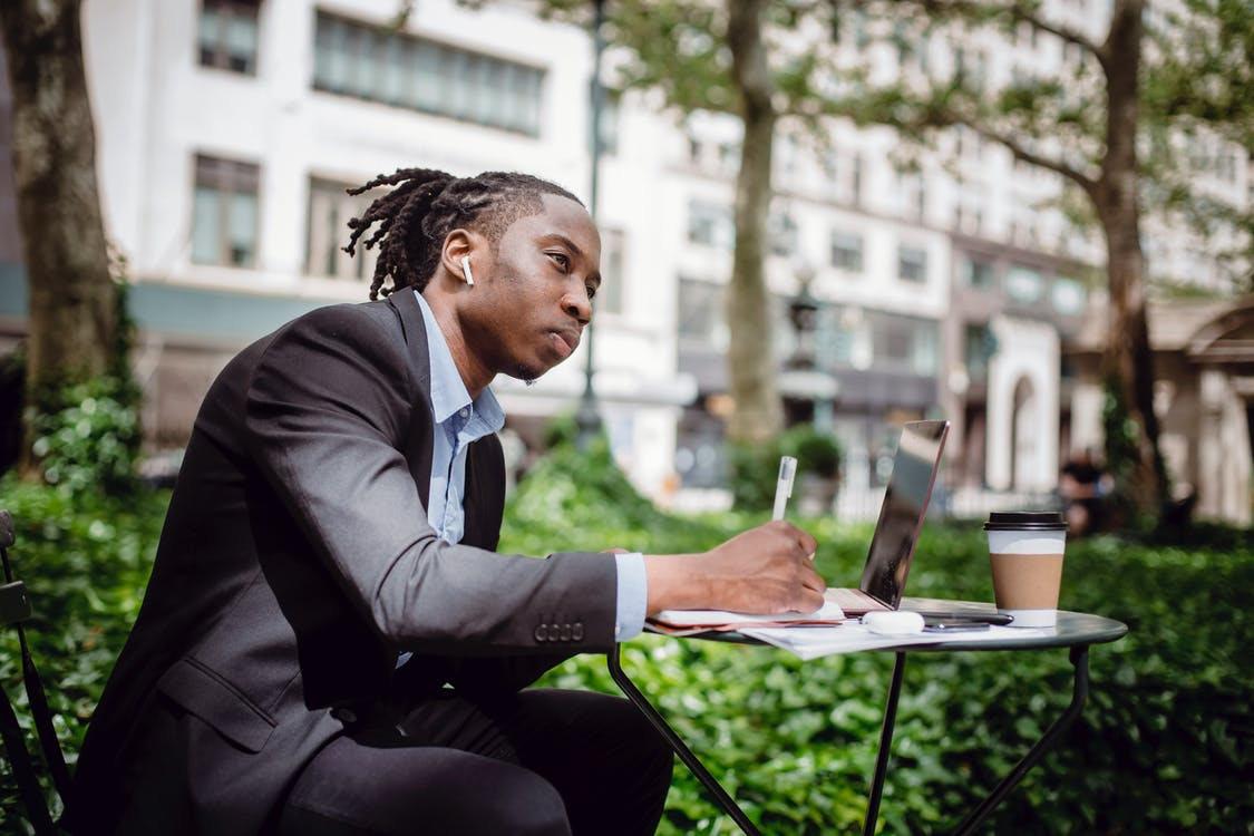 Pensive African American journalist writing thoughts in notebook sitting in outdoor cafeteria