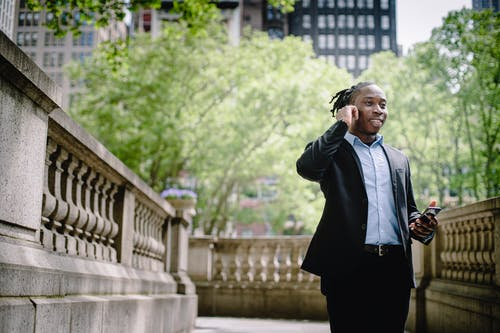 Happy young African American male manager in formal suit with smartphone answering call with wireless earphones against modern buildings in business district