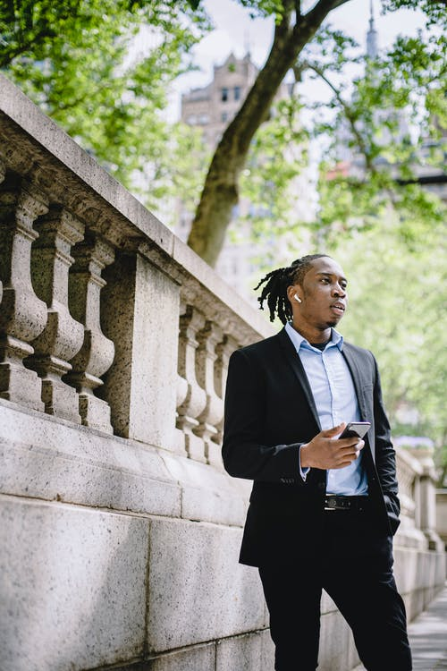From below of serious young black male entrepreneur with dreadlocks in classy suit checking time on smartphone and waiting for meeting in city park