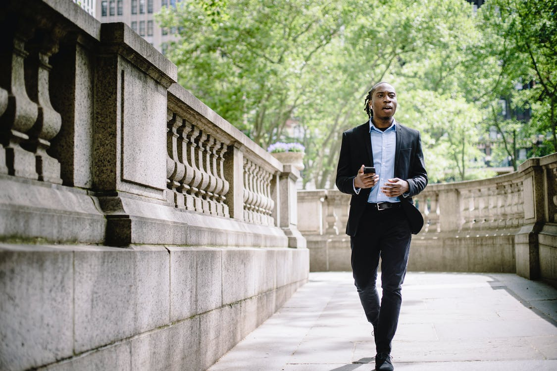 Focused black manager going to work and talking on smartphone via wireless earphones