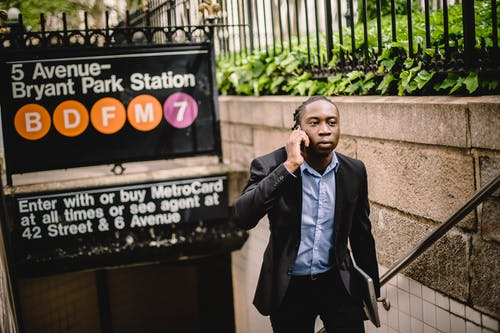 Serious black businessman talking on smartphone while exiting subway