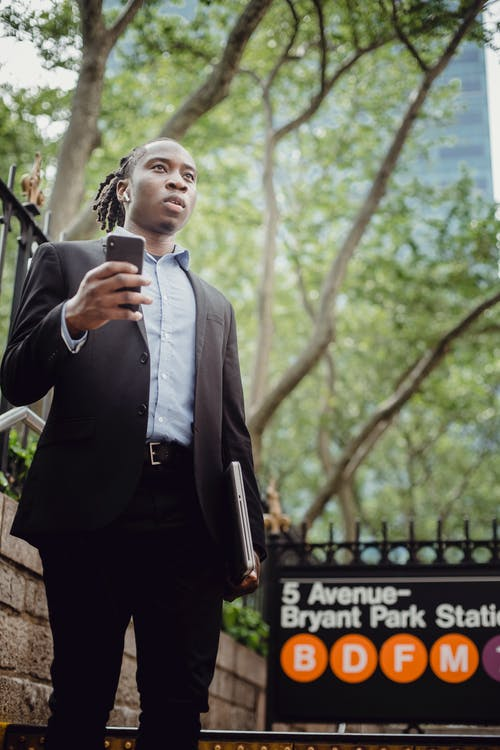 Low angle of serious black male in formal wear listening to music on cellphone through wireless earbuds while standing with laptop in hand on New York street