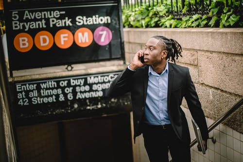 Young black office worker in smart suit with dreadlocks talking on cellphone while exiting subway on summer day in New York