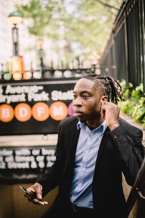 Young black office worker listening to music through wireless earbuds