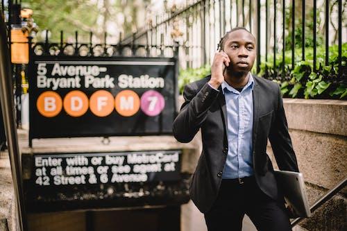 Serious black businessman talking on smartphone on street