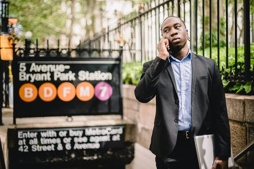 Serious African American businessman wearing formal suit having phone call while standing near New York metro station and looking away thoughtfully