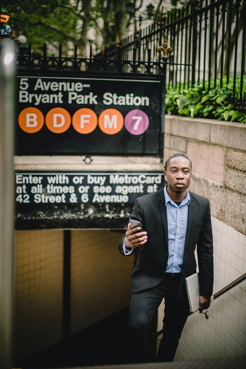 Confident black businessman in black formal wear using mobile phone while exiting metro station in New York on summer day
