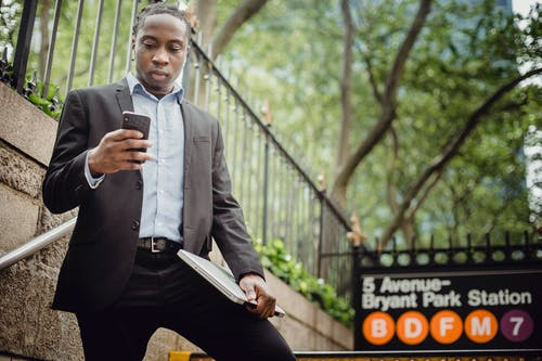 From below confident African American businessman wearing formal clothes browsing modern mobile phone while standing on stairs near New York metro station
