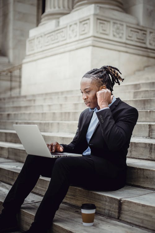 Positive African American businessman in suit sitting on stairs of modern stone building while working on netbook and putting on wireless earbuds