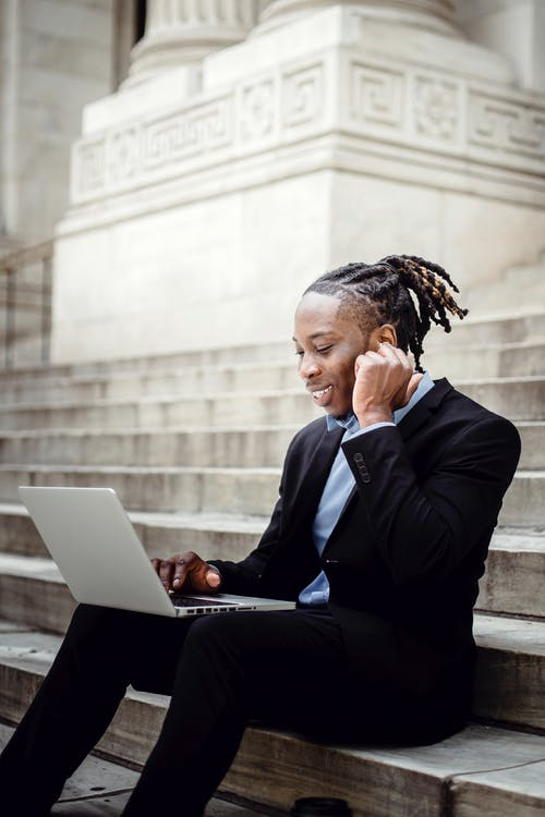 Happy black businessman with earbuds and laptop on building staircase