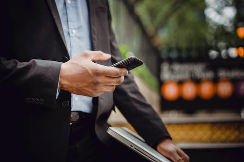 Crop black businessman using smartphone on street