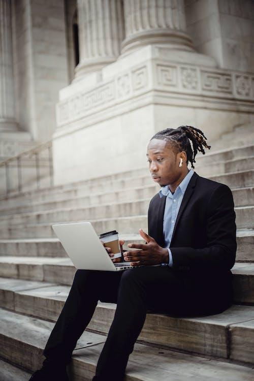 Surprised black businessman having video call via laptop on stairs