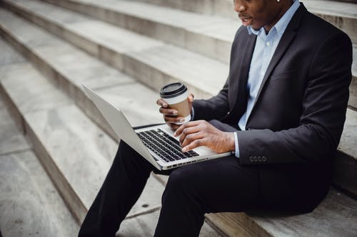 Crop positive African American businessman wearing formal outfit sitting on stone stairs with paper cup of hot drink while working on project on laptop