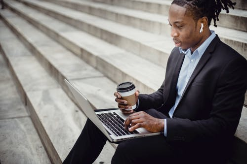 Crop content black businessman typing on laptop on stone stairs
