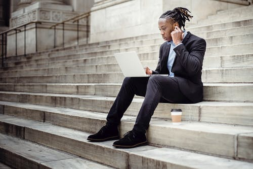 Full length focused African American businessman in formal black suit sitting on stone staircase of modern building and browsing netbook while putting on wireless earbuds