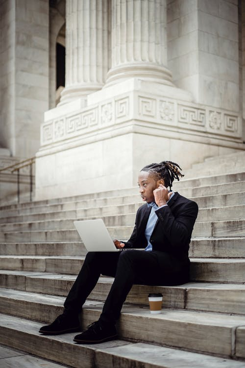 Thoughtful businessman with laptop and earbuds on stairs
