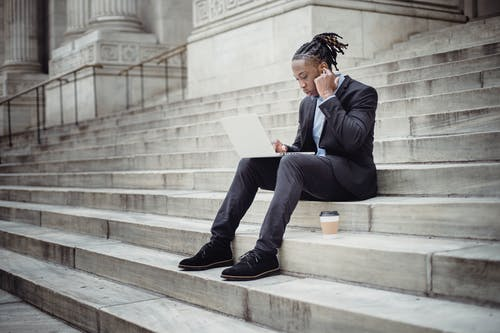 Full length focused black businessman in formal suit browsing modern netbook and using wireless earbuds while resting on stone building steps