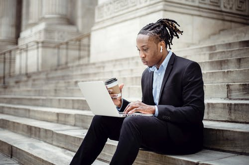Concentrated African American businessman wearing formal clothes with coffee to go and earbuds browsing netbook while working remotely on stone building stairs