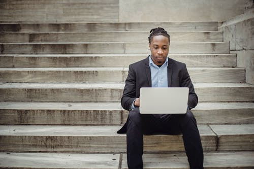 Focused black businessman working on laptop remotely on street steps