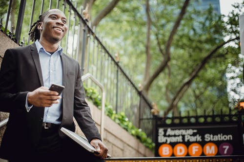 Low angle positive African American businessman in formal black suit with cellphone and laptop standing near New York metro station and looking away happily