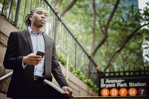 Thoughtful African American businessman using smartphone near metro station