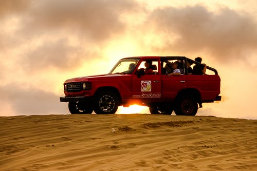 People Riding a Red 4x4 Vehicle on Desert