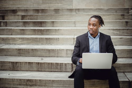 Positive young black businessman using laptop on stairs