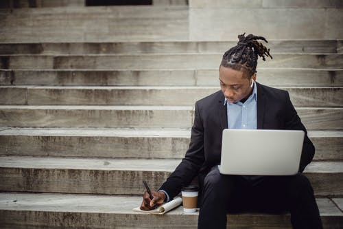 Serious ethnic male manager taking notes while working on netbook on steps