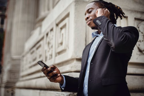 Low angle of happy young black guy in formal wear browsing mobile phone and enjoying music in true wireless earphones while standing on street near modern building