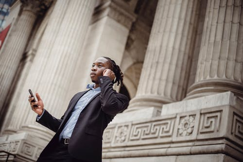From below of young concentrated black male manager in suit talking on smartphone using wireless earphones against pillared building