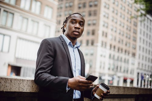 Pensive young black businessman in elegant suit looking away while standing against blurred modern buildings with smartphone and coffee to go
