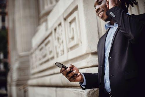 Smiling black male manager communicating on smartphone outside modern building