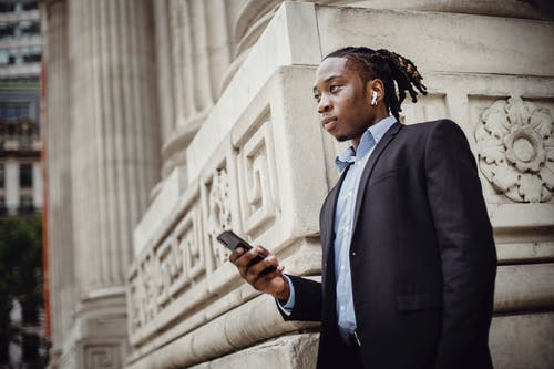 Pensive black businessman waiting on street with smartphone in hand