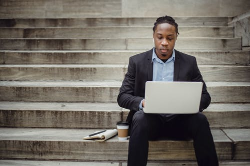 Thoughtful black male employee typing on laptop sitting on stairway