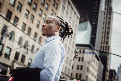 Young African American male standing on sidewalk in downtown against modern buildings