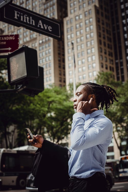 Confident ethnic entrepreneur talking on cellphone in downtown on sunny day