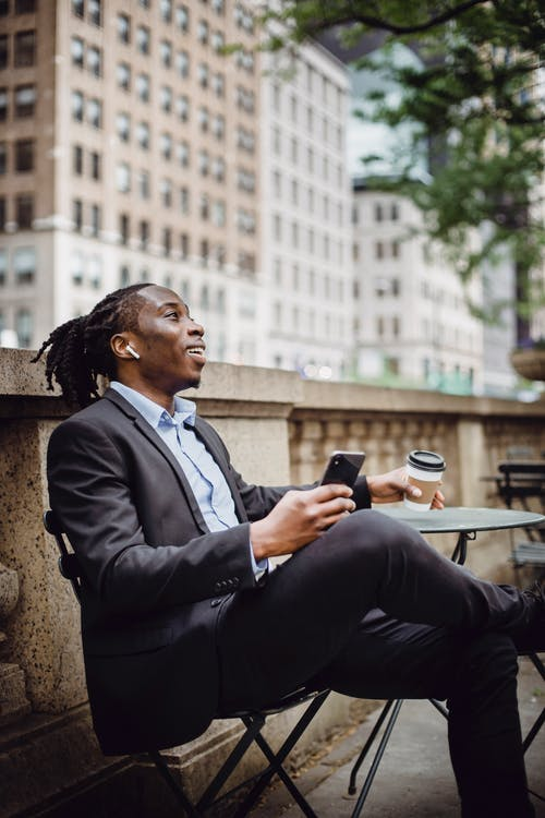 Side view of happy young African American male manager in suit relaxing on terrace of cafe with smartphone and cup of takeaway coffee