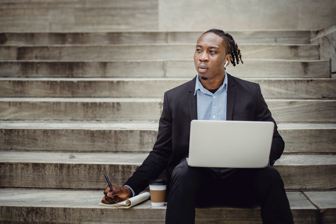 Thoughtful black worker using netbook and taking notes sitting on steps