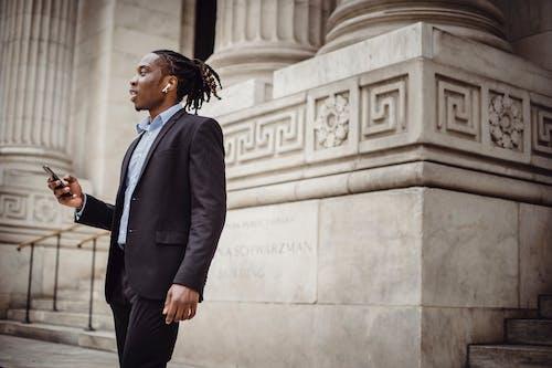 Elegant black businessman using TWS earphones while talking on smartphone against pillared building