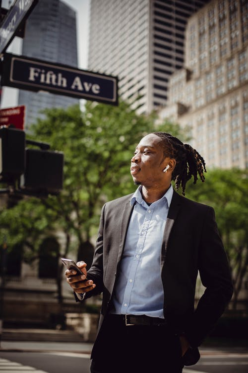 Young black office employee in smart suit with dreadlocks in ponytail and wireless earbuds in ears listening to music on smartphone while standing on street in Manhattan on sunny summer day