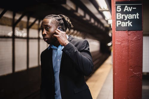 African American male in formal wear talking on mobile phone and looking into subway tunnel with worried expression on face while waiting for train at empty New York metro station