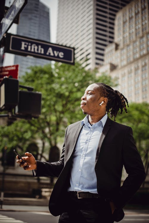 Young African American man in smart suit with dreadlocks and wireless earphones listening to music on smartphone while standing on street in Manhattan on sunny day