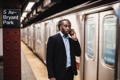 Serious African American male in formal suit talking on smartphone while waiting for underground train to stop