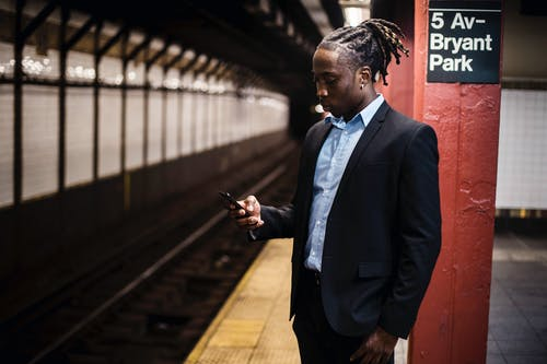 Modern young African American man in office suit text messaging on cellphone while waiting for train at Manhattan subway station